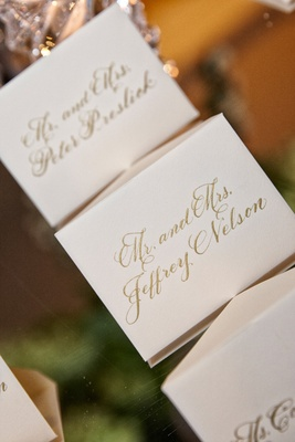 small white place seating cards with gold calligraphy