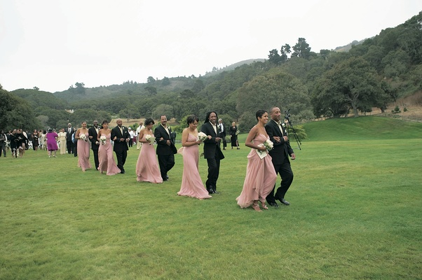 Bridesmaids and groomsmen cross grass lawn