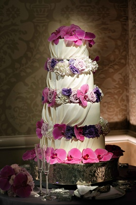 Wedding cake with draped and gathered white fondant with fresh purple flowers