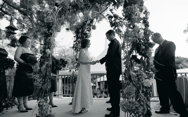 Black and white photo of bride and groom at outdoor ceremony
