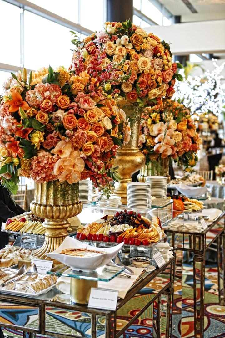 Appetizer table decorated with large golden urns filled with yellow, orange, and red flowers