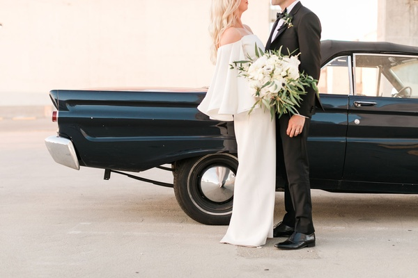 Bride in white off shoulder wedding dress groom in tuxedo black old classic car mustang on roof