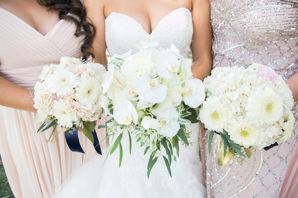 bride bridesmaid bouquets white pink daisies leaves green orchids
