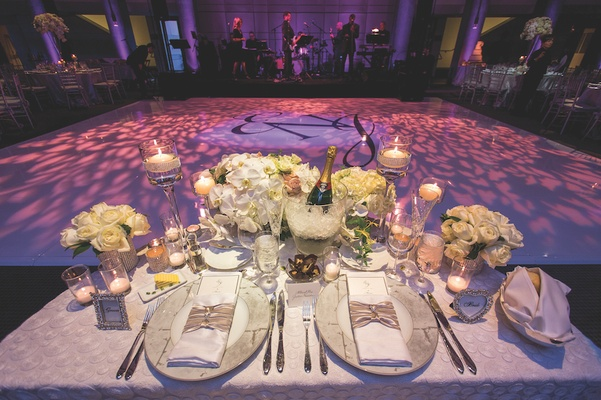 Table with ivory flowers and view of the dance floor