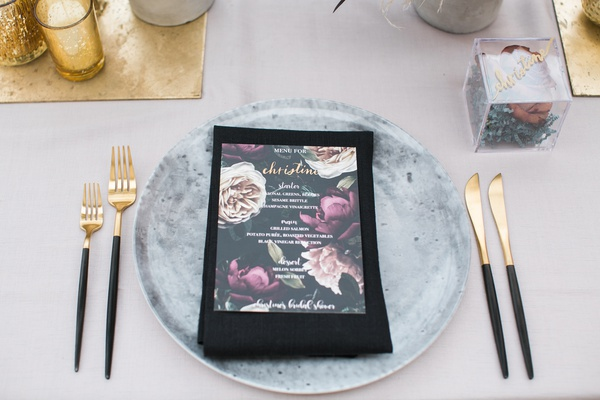 bridal shower with grey charger plate designed to look like concrete, gold flatware black handles