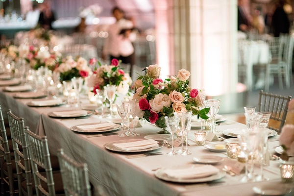 Long wedding reception table silver chairs and linens low centerpieces pink roses and peonies