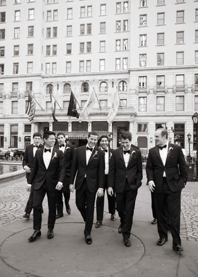 Black and white photo of groom with groomsmen in tuxedos outside courtyard of The Plaza Hotel NYC