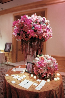 escort card table topped with two pink flower arrangements