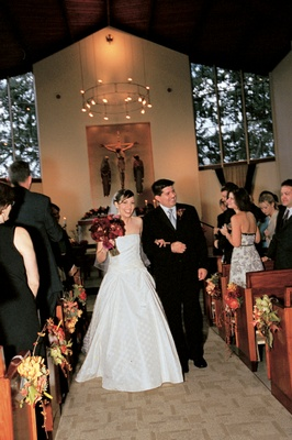 bride and groom walk down aisle lined with autumn inspired flowers