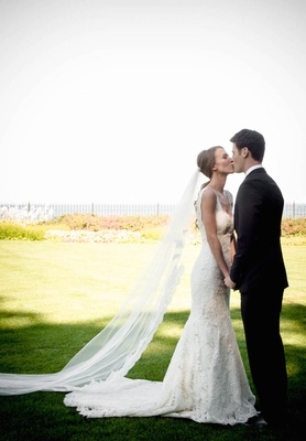 Bride in Ines Di Santo lace dress kisses groom in tux