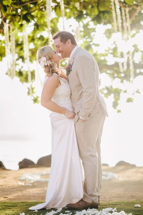 Man in khaki suit and brown shoes kissing bride