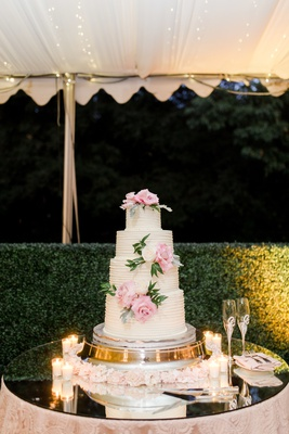 four tier wedding cake with pink flowers and greenery on mirror table