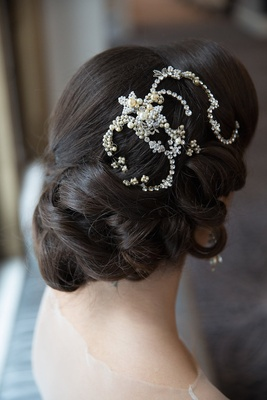 Bride with updo wedding hairstyle and swirl headpiece with crystals and pearls