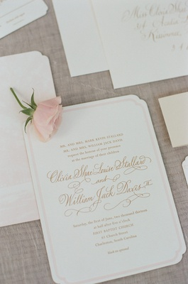 Light pink-bordered wedding invites and rose