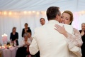 Bride and groom in white dance at tented wedding reception