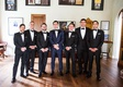 groom in navy suit and groomsmen in black white tuxedos bow ties in man cave pool table sports