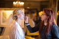 Bride with blonde hairstyle getting lips done by makeup artist