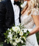 Bride in jewel cap sleeve wedding dress kissing groom bouquet white dahlia, ranunculus, garden rose