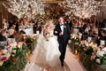 Indoor wedding with flowering trees and lush aisle