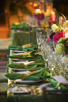 Reception table with green tablecloth and napkins