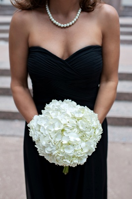 Woman in black gown holding white hydrangeas