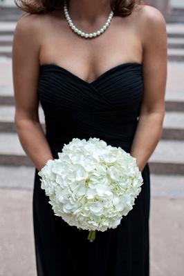 Woman in black gown holding white hydrangeas