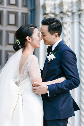 bride with low bun and veil below with pretty bow dress and ceremony top groom in navy blue suit