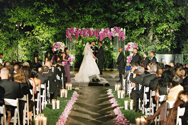 Purple wedding flowers at outdoor wedding ceremony and on Lucite gazebo at Four Seasons