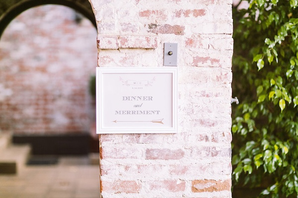 Sign in white frame with arrow on brick wall pointing to outdoor wedding reception