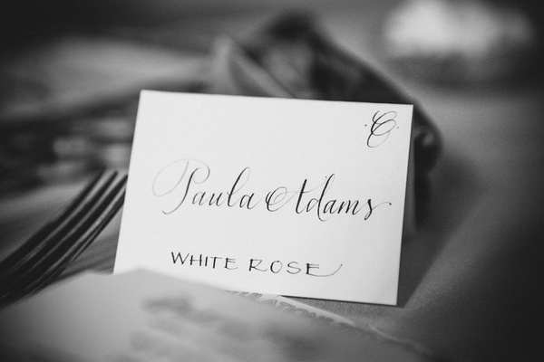 Black and white photo of a wedding reception escort card with calligraphy and flower table name