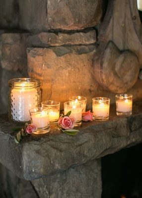 Wedding reception in adobe room of San Ysidro Ranch with candles, pink roses, leaves on mantle