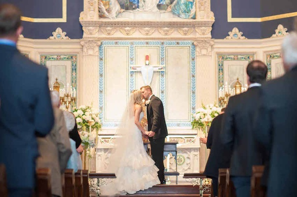 Running back Brian Leonard in a black tuxedo kisses his bride in an Isabelle Armstrong dress