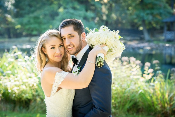 Bride holding wedding bouquet with hands on groom shoulders off shoulder strap anne barge gown