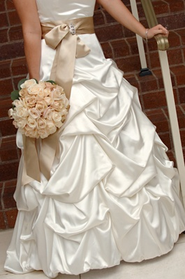 Bridal gown with tan belt and flowers