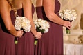 Bridesmaids in purple strapless dresses hold bouquets of white roses, calla lilies wrapped in purple