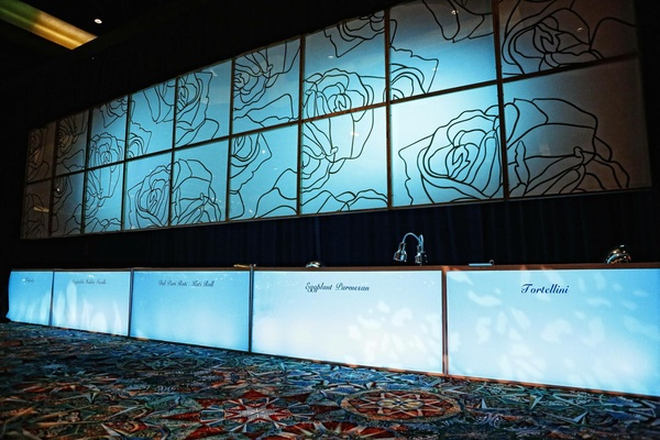 Wedding reception buffet with decorative panels with rose pattern above and dish names below