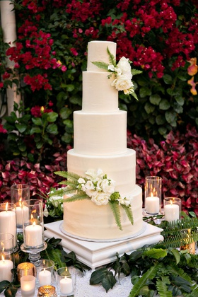 wedding cake in front of bougainvillea bush white ivory round layers fresh greenery flowers candles