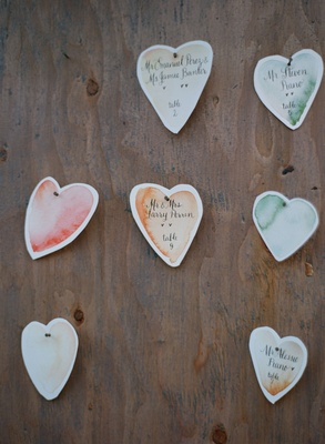 Heart-shaped seating cards with watercolor design and calligraphy