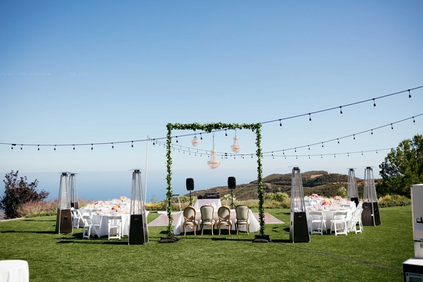 outdoor reception, string lights, greenery arch,