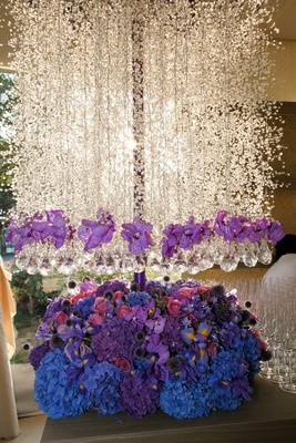 tall floral arrangement featuring blue pink and purple flowers and hanging white flowers crystals