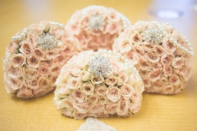 Pale pink rose bouquets with strands of pearls & rhinestone brooches for bridesmaids