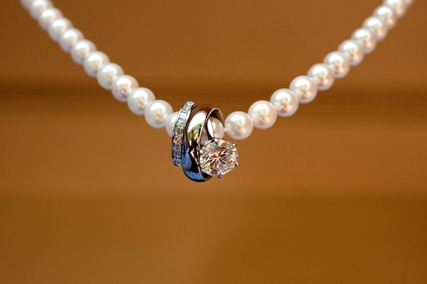 Solitaire engagement ring and diamond band on strand of pearls