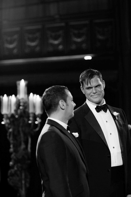 Black and white photo of Matthew Christopher in a tuxedo with his groom at ceremony