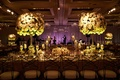Purple lighting at live band wedding reception stage with long king's table high centerpieces candle