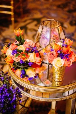 sangeet decoration with bright orange, purple, yellow flowers, and glass lantern