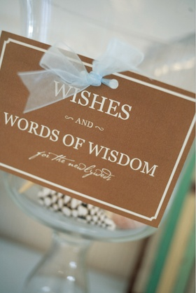 Gold and white sign with light blue ribbon for wishes and wisdom