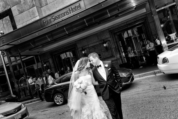 Black and white photo of bride and groom in Chicago smiling and touching foreheads
