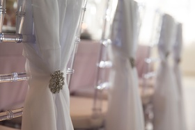 Clear chiavari chair reception table with white chair cover sash drapery silver brooch decal