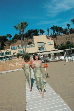 two bridesmaids in green dresses walk on wood plank aisle on sand