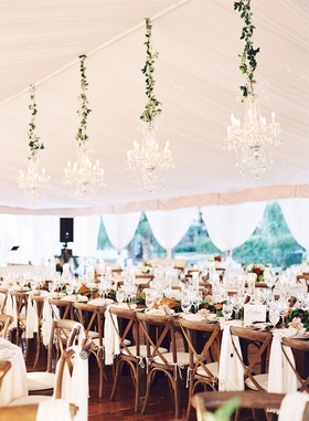 Wedding head table wood x back chairs white linens magnolia leaves greenery crystal chandeliers